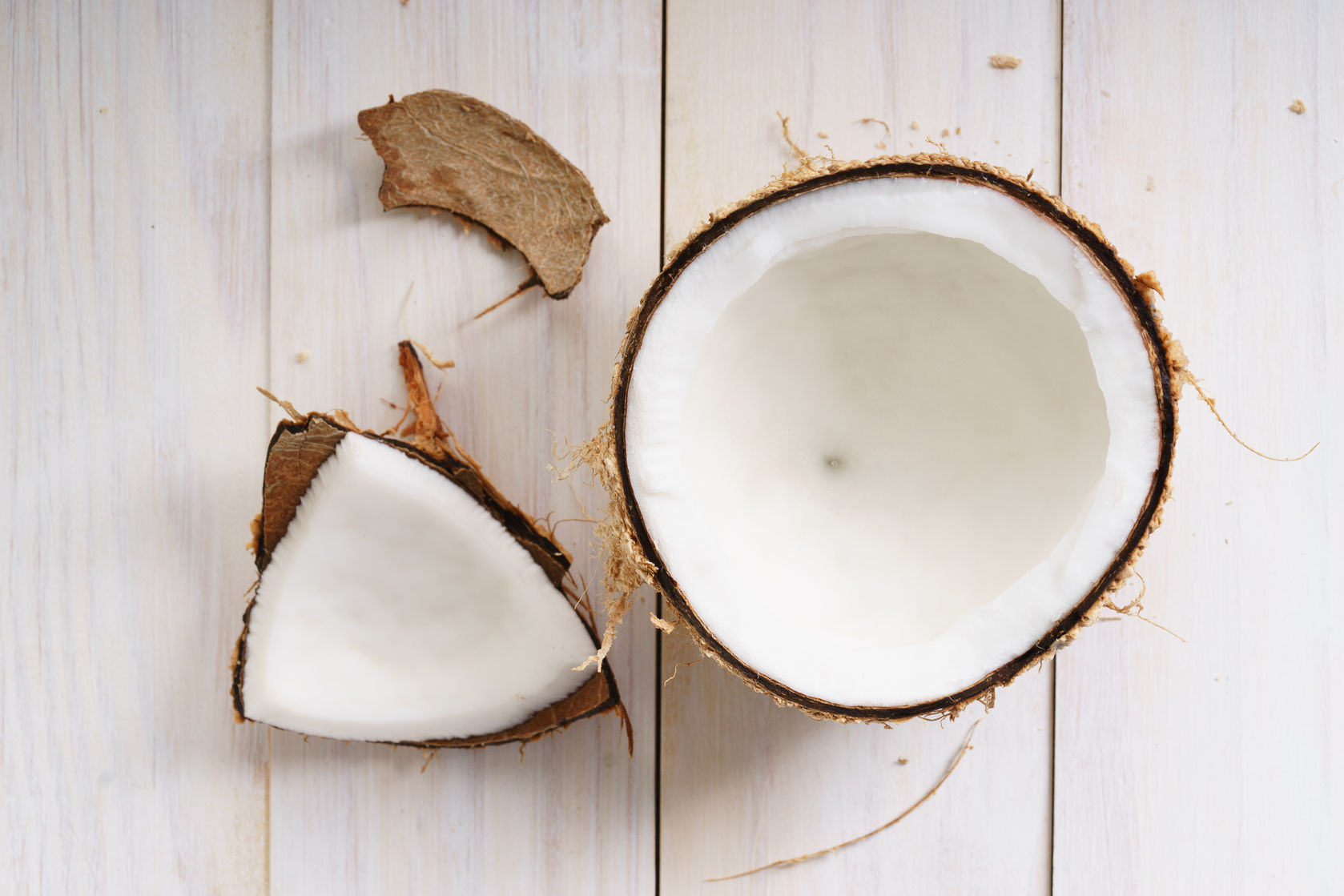 56624076 – coconut with shell on white wooden background
